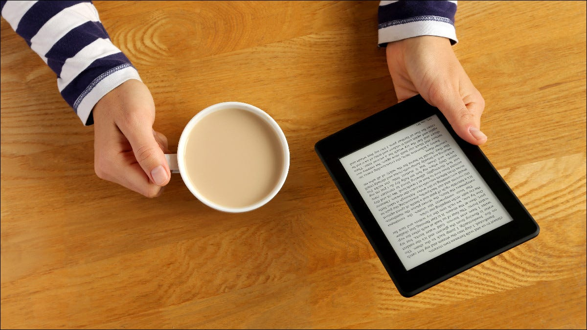 Person reading Kindle while drinking coffee.
