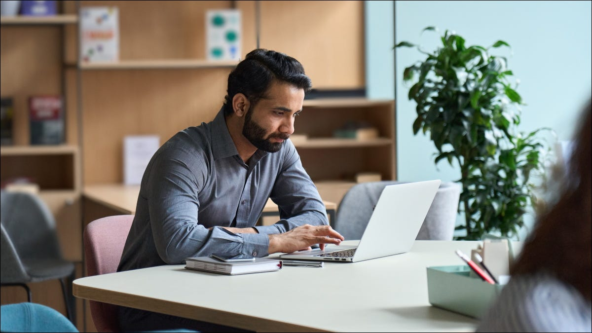 A man working at a laptop in an office.