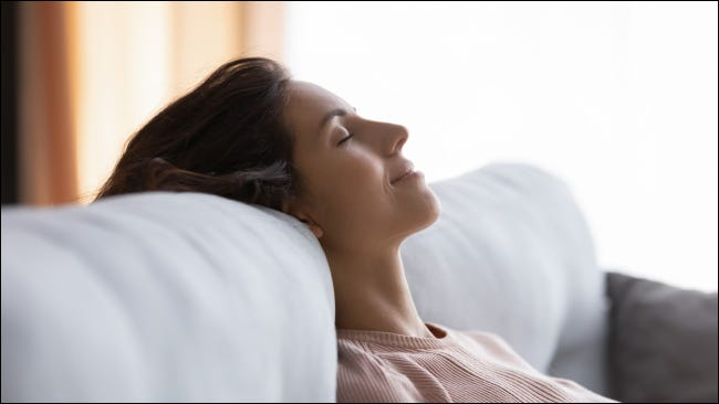 A woman relaxing on her couch with her eyes closed.