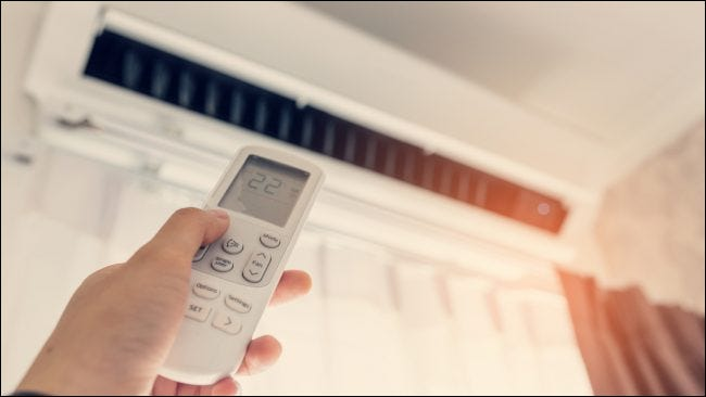 A hand pointing a remote control at an air conditioner