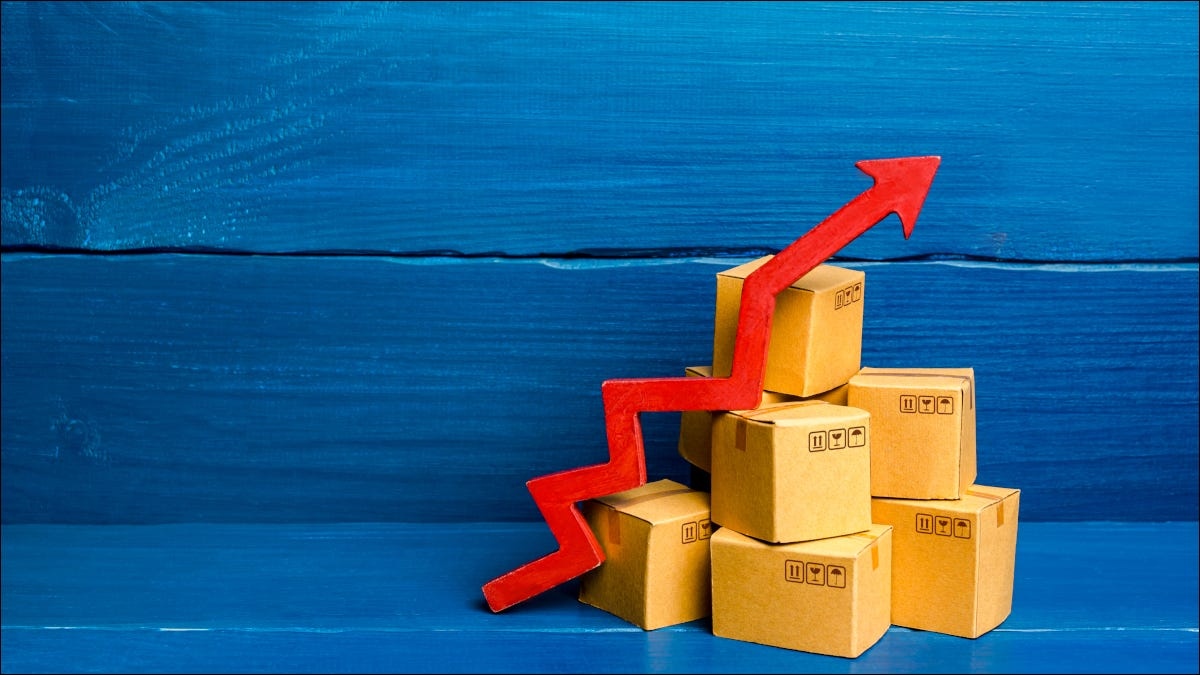 Red arrow rising over cardboard shipping boxes in a blue backdrop
