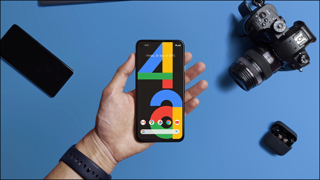 person holding pixel 4a over blue table