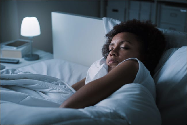 A woman sleeping in her bed at night.