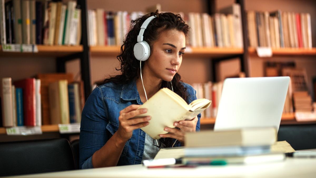 Студент учится на ноутбуке в библиотеке.