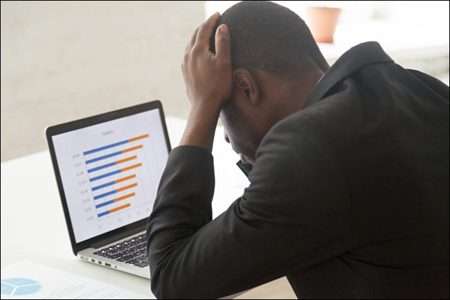 A man looking frustrated in front of a laptop.