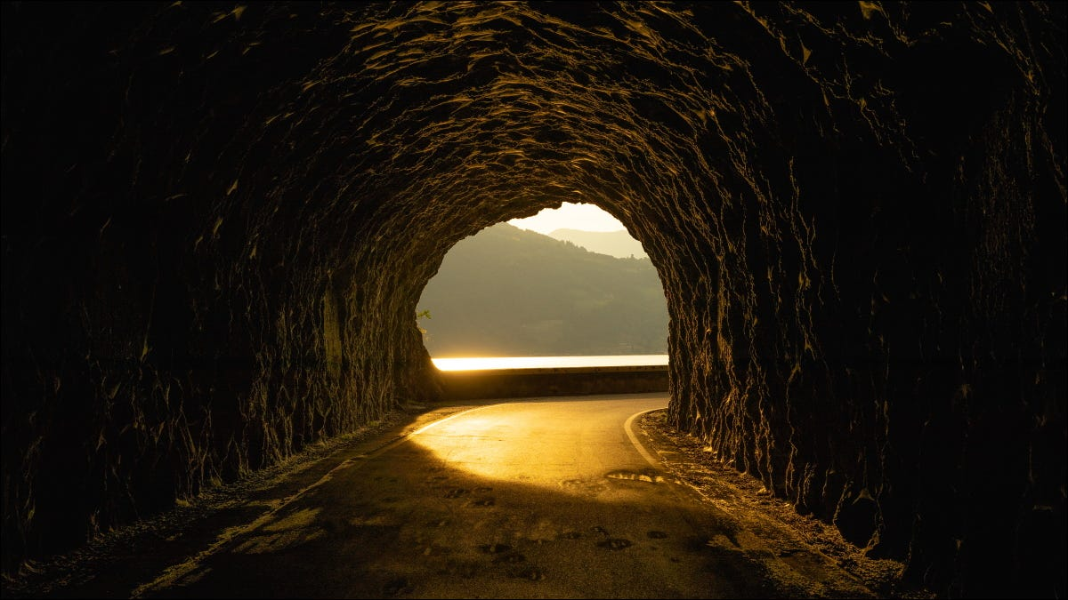 A rocky tunnel with a sunset on the other side of it.