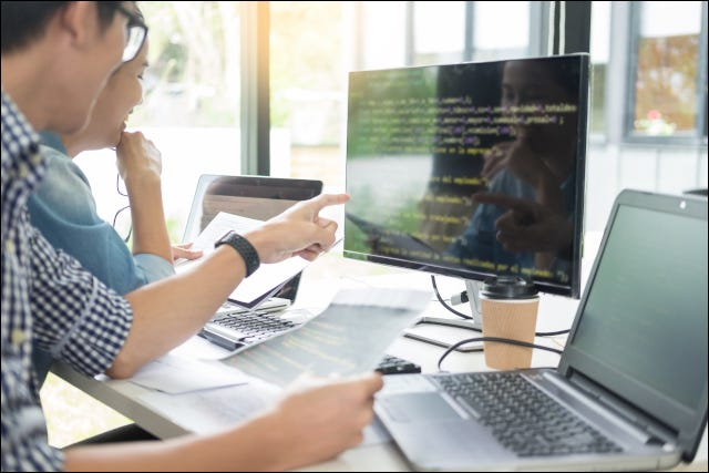 Two people coding together on a computer