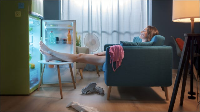 Woman cooling herself in front of a refrigerator