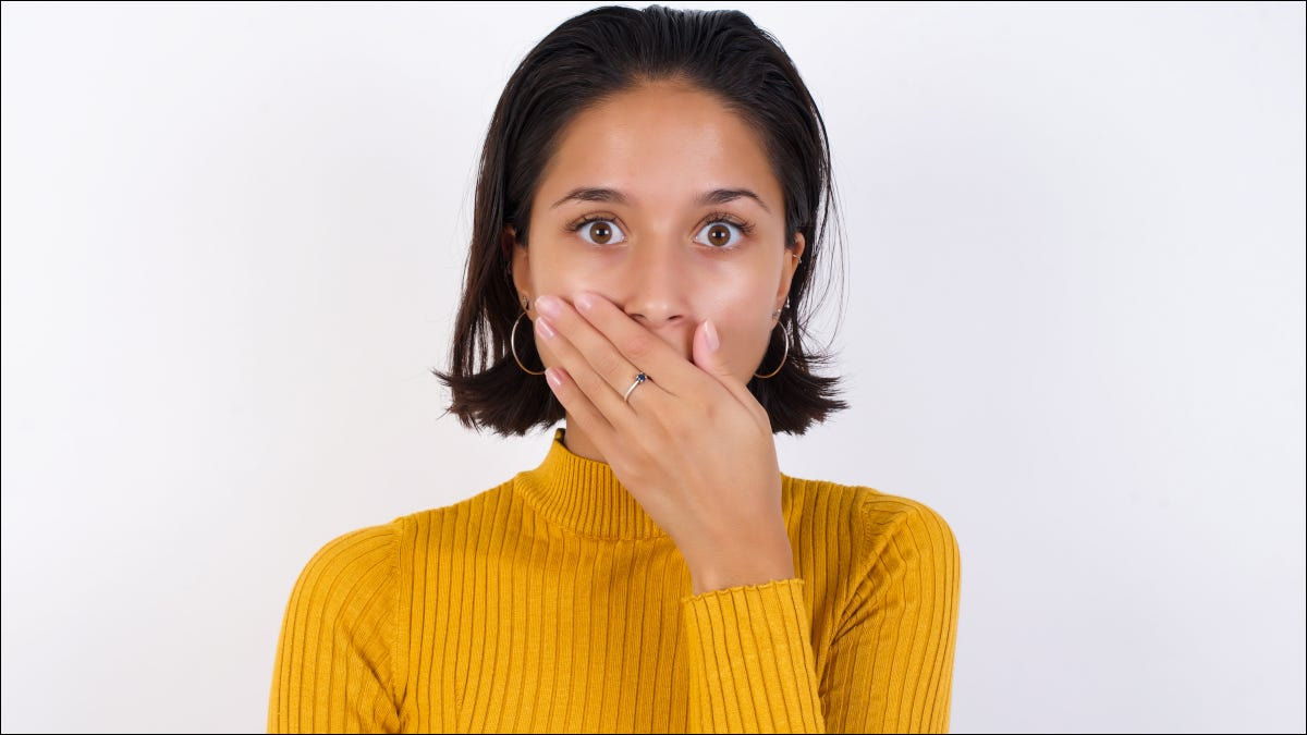 Woman with shocked expression and hand over mouth