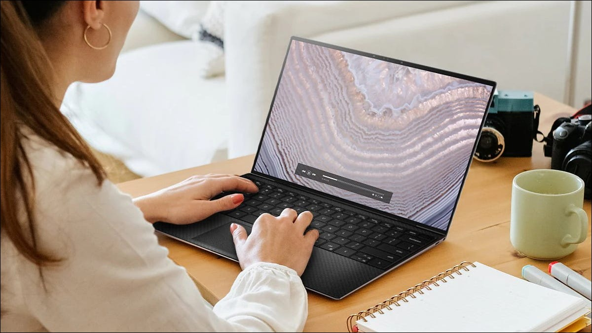 A woman using a Dell XPS 13 laptop at a desk.