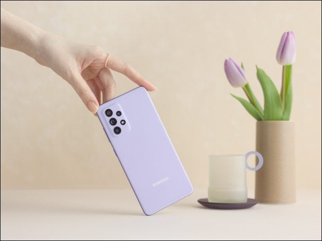 A purple Samsung A52 held by hand