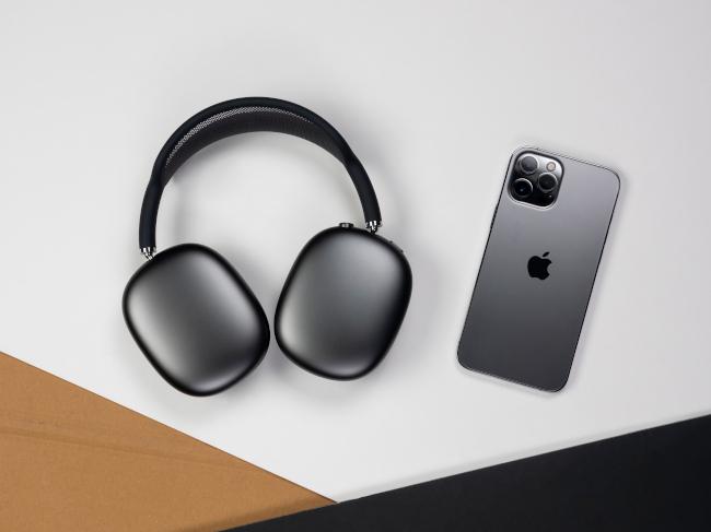 AirPods Max e iPhone neri appoggiati alla superficie di un tavolo.