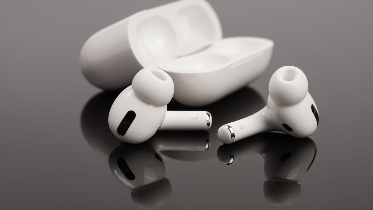 Apple Airpods and case on a dark reflective surface