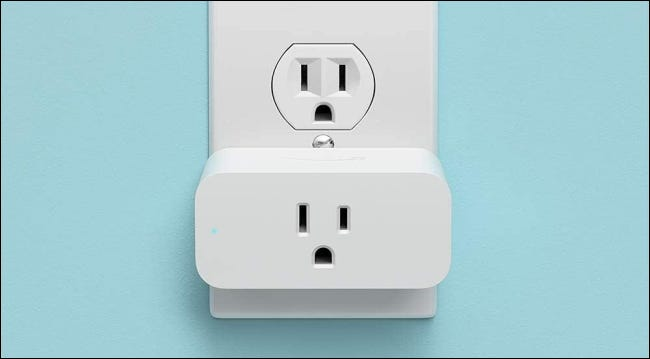 Amazon smart plug in outlet on blue background