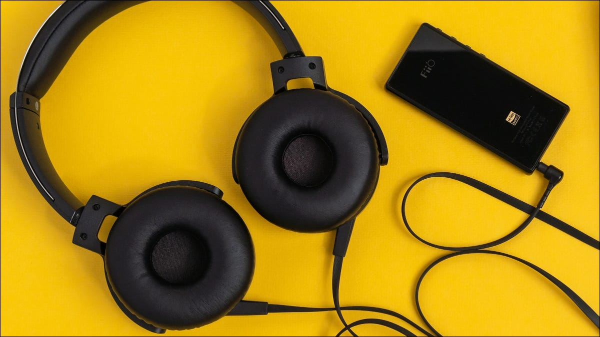Black wired headphones and audio player on a yellow surface