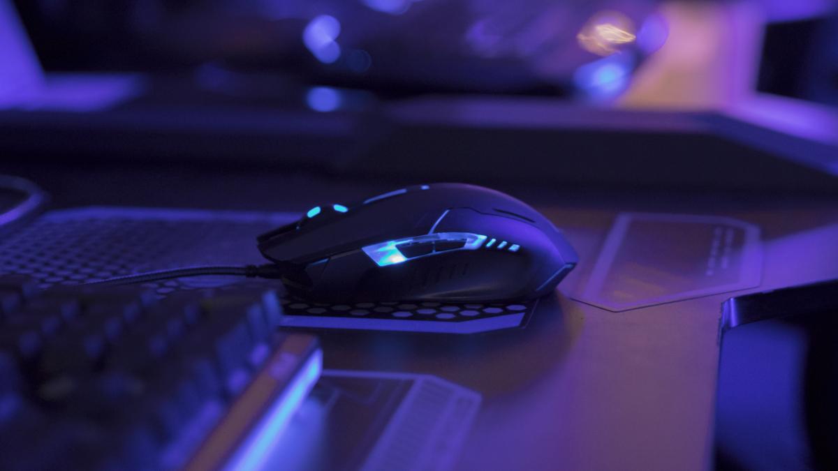 Lit up gaming mouse on computer desk in blue light