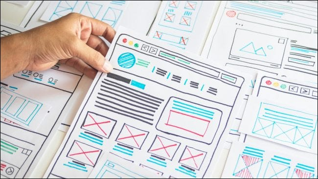 Hand holding a paper with colorful UX designs