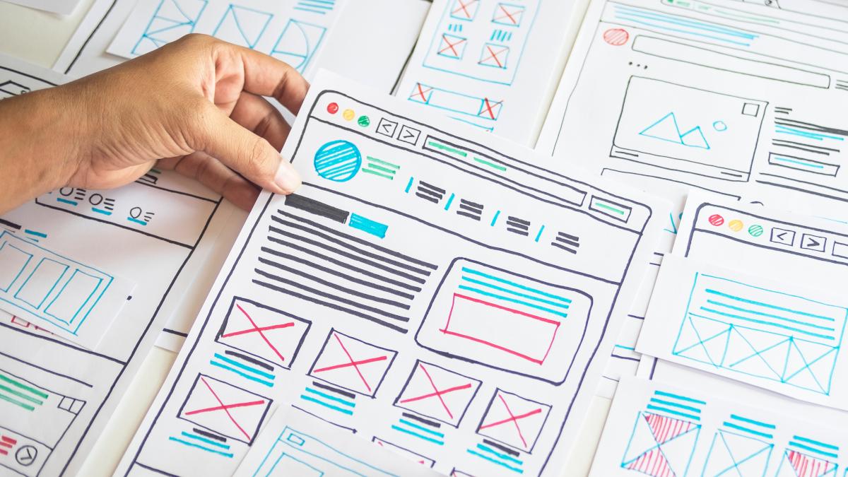 Mão segurando um papel com designs coloridos de experiência do usuário