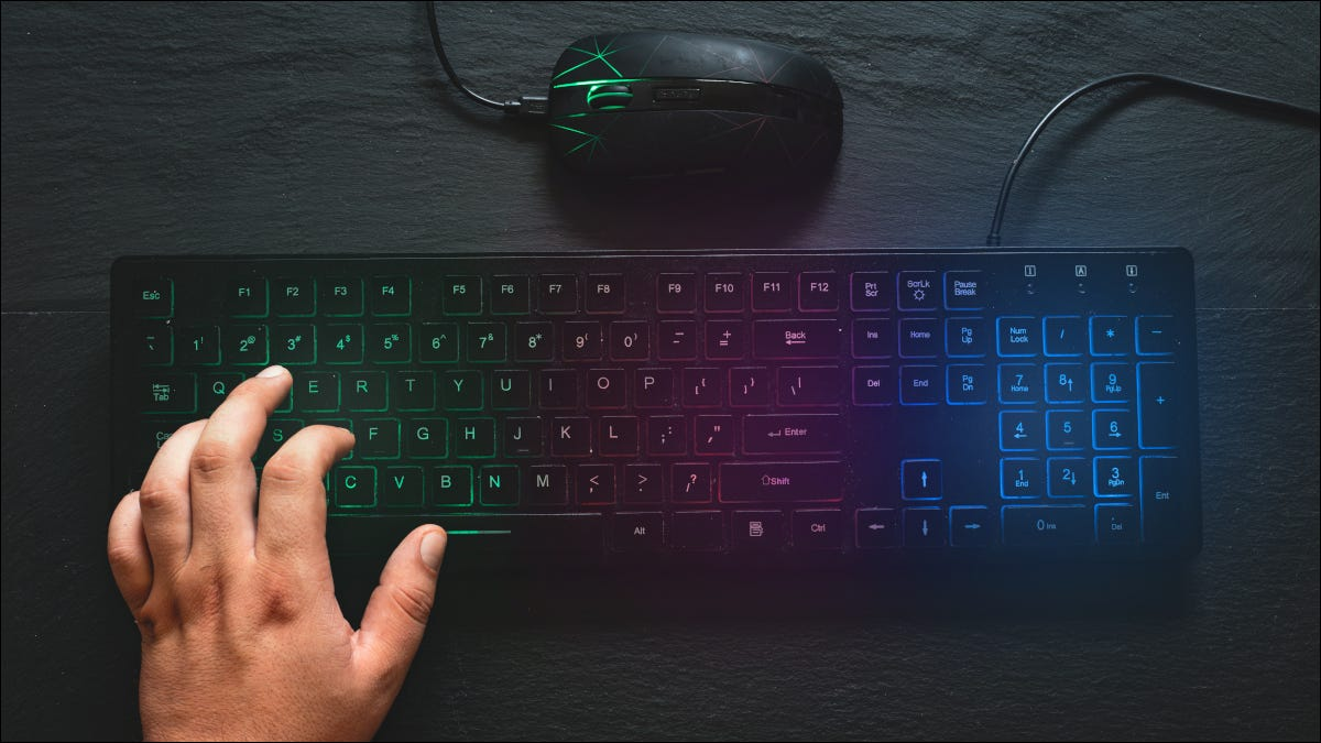 RGB colored keyboard and mouse with hand on the keyboard