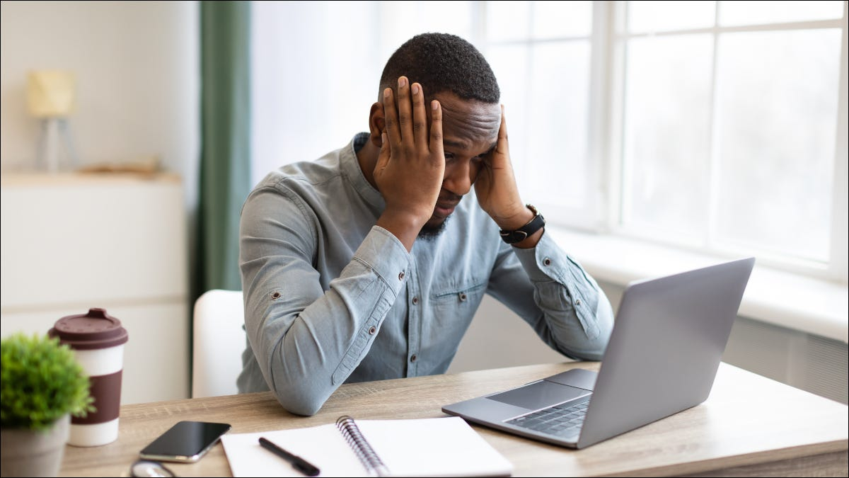 Man sitting at desktop with laptop, clutching his head in frustration