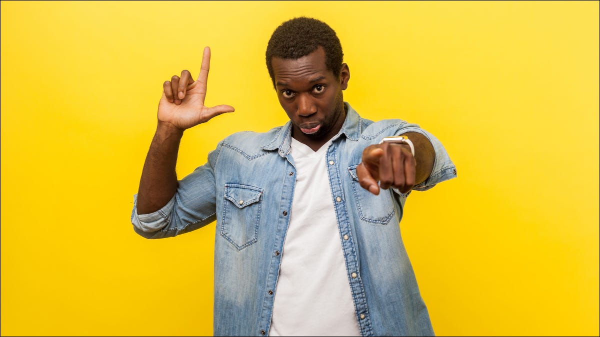 Man pointing with loser hand gesture on yellow backdrop