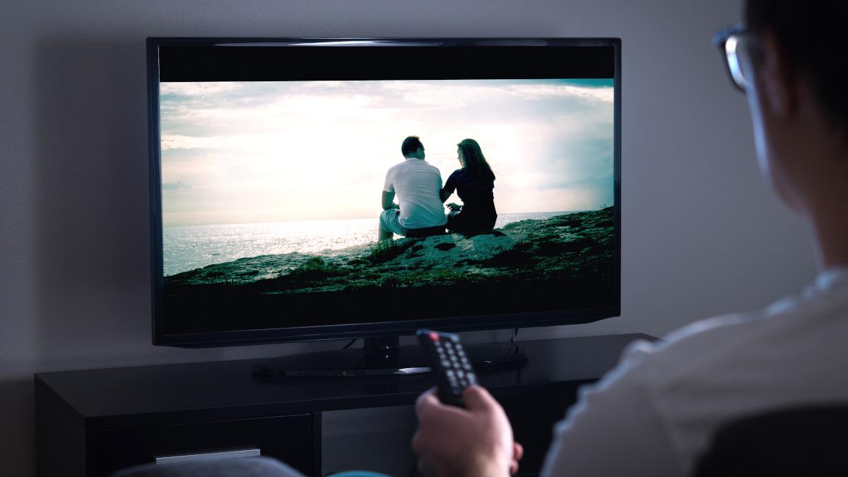 Man pointing remote at TV
