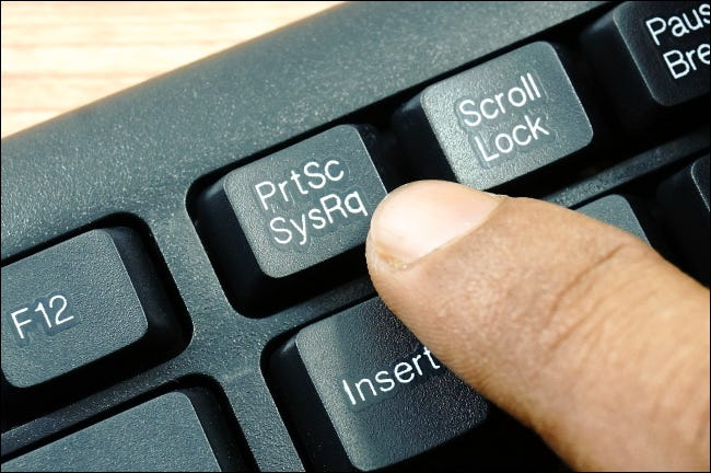 A finger pressing the PrtSc key on the top row of a PC keyboard.