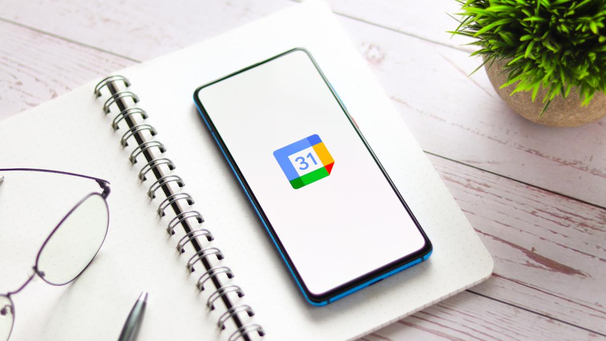 Smartphone on open planner with Google Calendar logo displayed