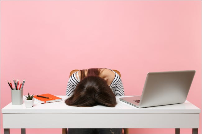 Exhausted woman with face planted on desk next to computer and office supplies.