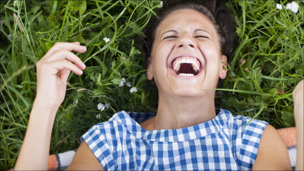 Woman rolling on grass laughing.