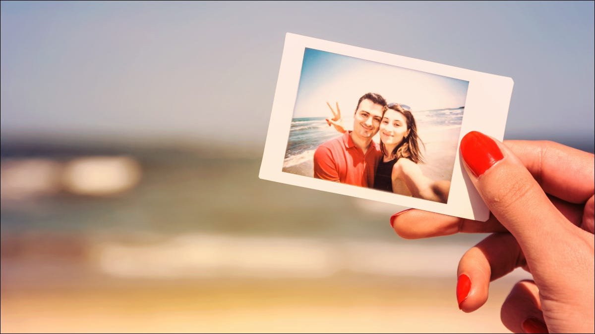 Woman's hand holding photograph of couple in front of beach