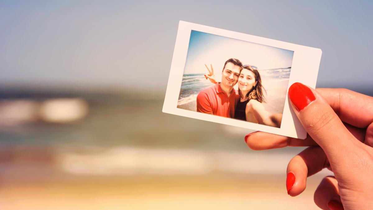 Женская рука держит фотографию пары перед пляжем