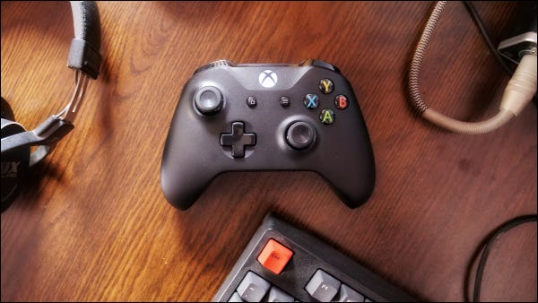Xbox One controller with headset and keyboard on wood surface.