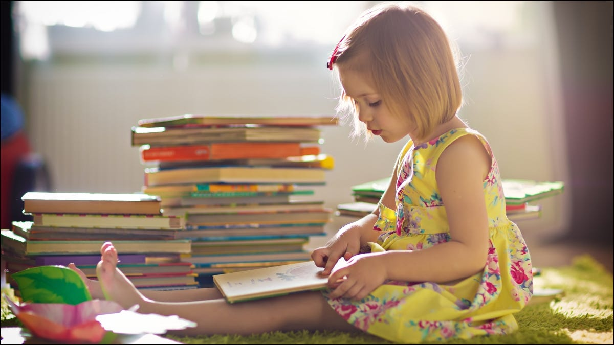 Young girl reading a book in front of a large stack of books