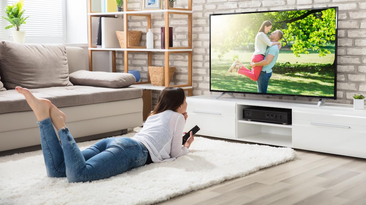 Young woman lying on floor watching TV