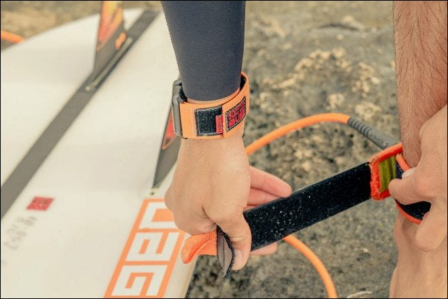 Person wearing UAG strap while preparing to surf