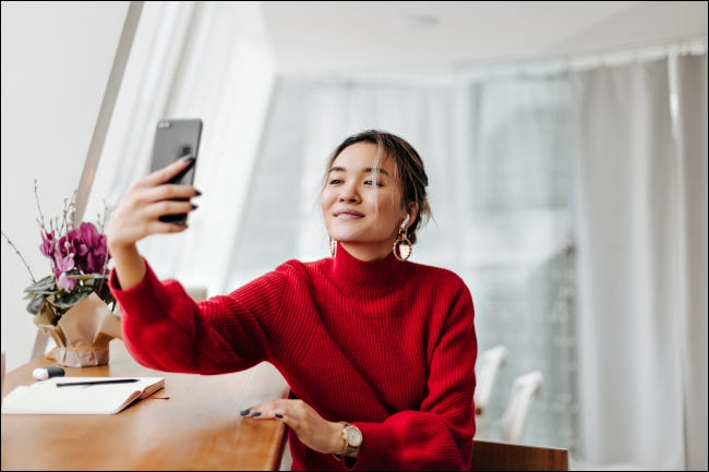 Woman in a red sweater taking a selfie in the natural light of a window