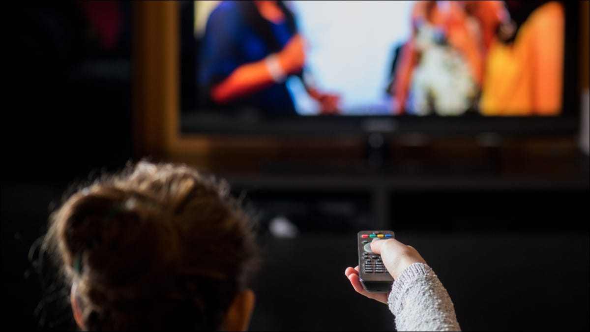 woman watching tv while holding remote