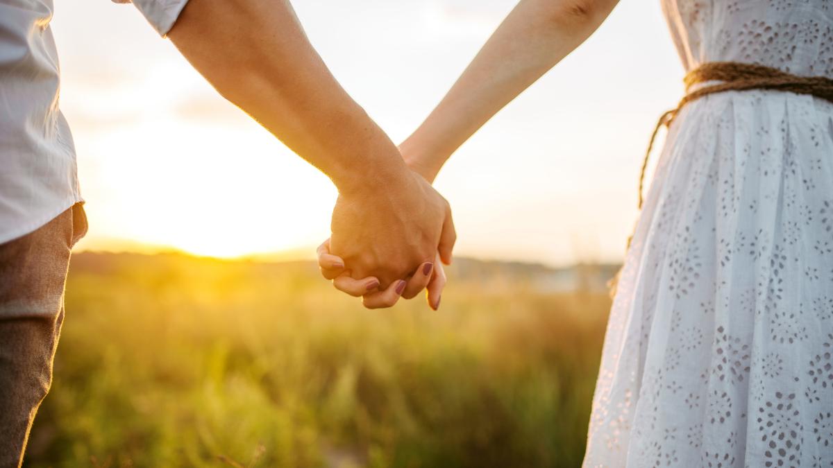 Closeup de casal de mãos dadas ao pôr do sol