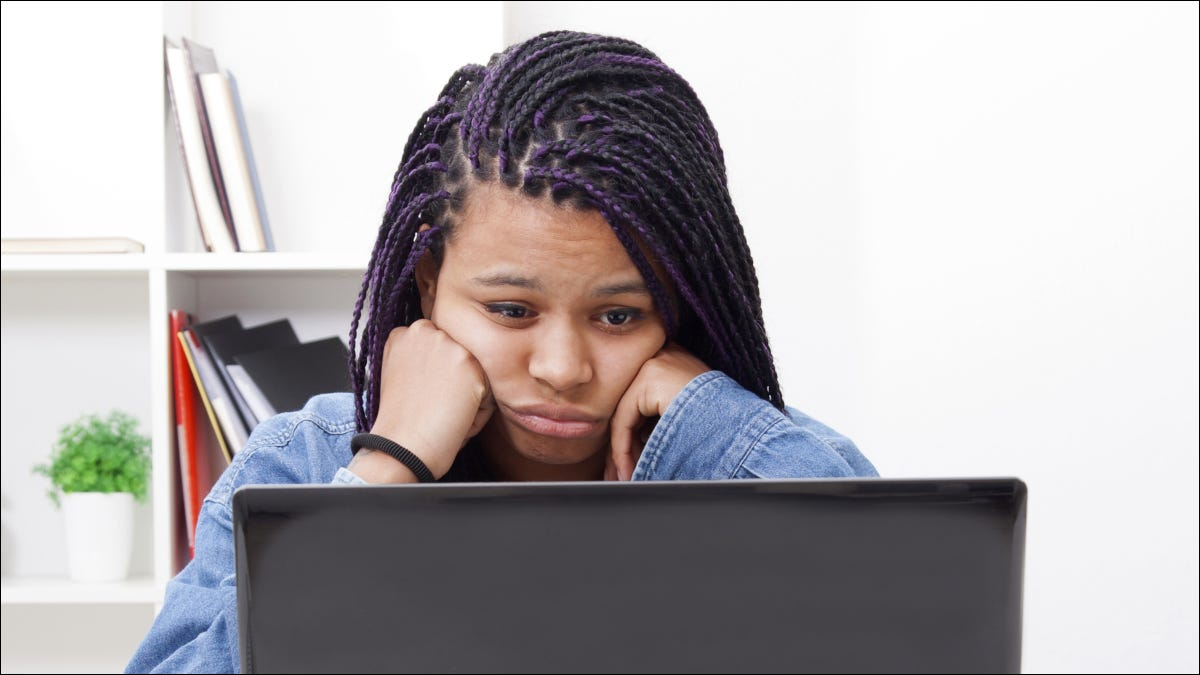 Woman looking at a laptop screen with tired look on her face.