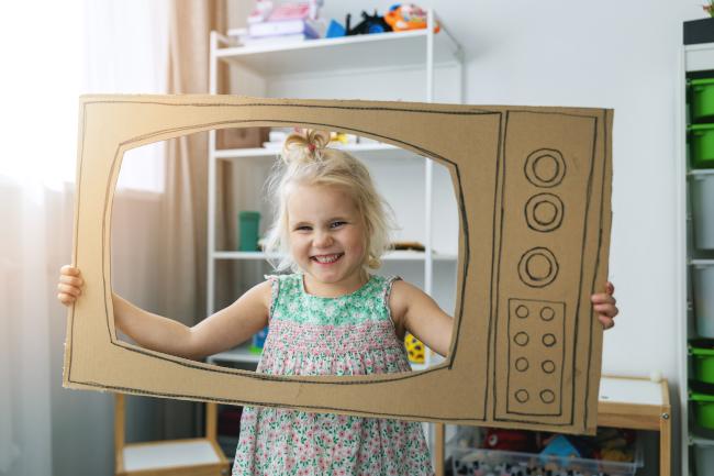 Smiling child inside a cardboard TV set