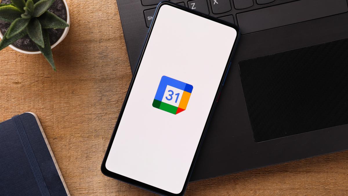 Google Takvim logosunun görüntülendiği bir dizüstü bilgisayarın üstünde akıllı telefon