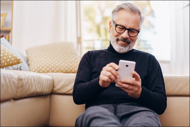 Man sitting and smiling at smartphone