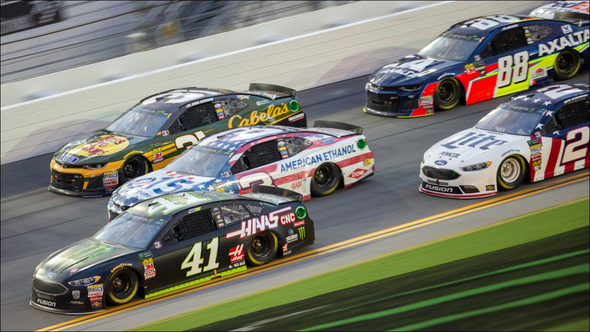 Nascar stock cars racing around a track