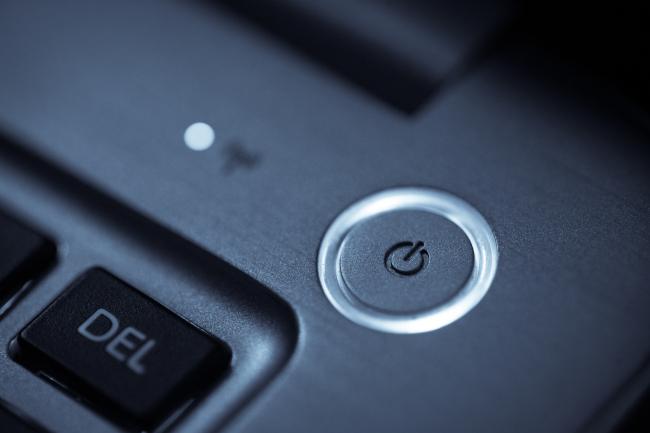 Close de um botão redondo de energia no canto de um teclado de laptop.