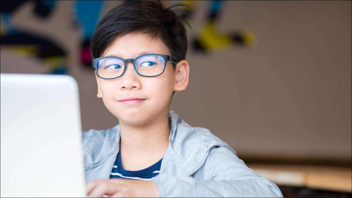 Preteen boy in glasses on a laptop smiling and rolling eyes