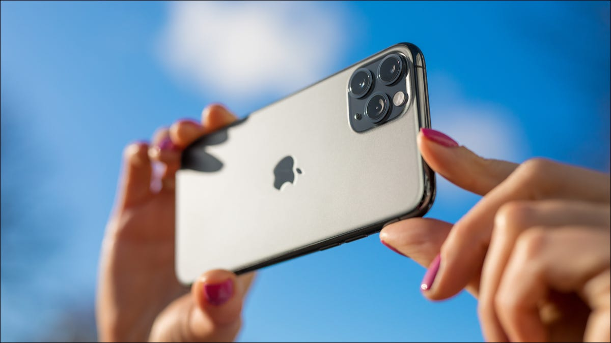 A person taking a photo outside with an iPhone.