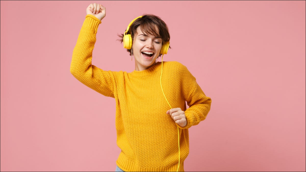 Woman in yellow sweater dancing while listening to music on yellow, wired headphones