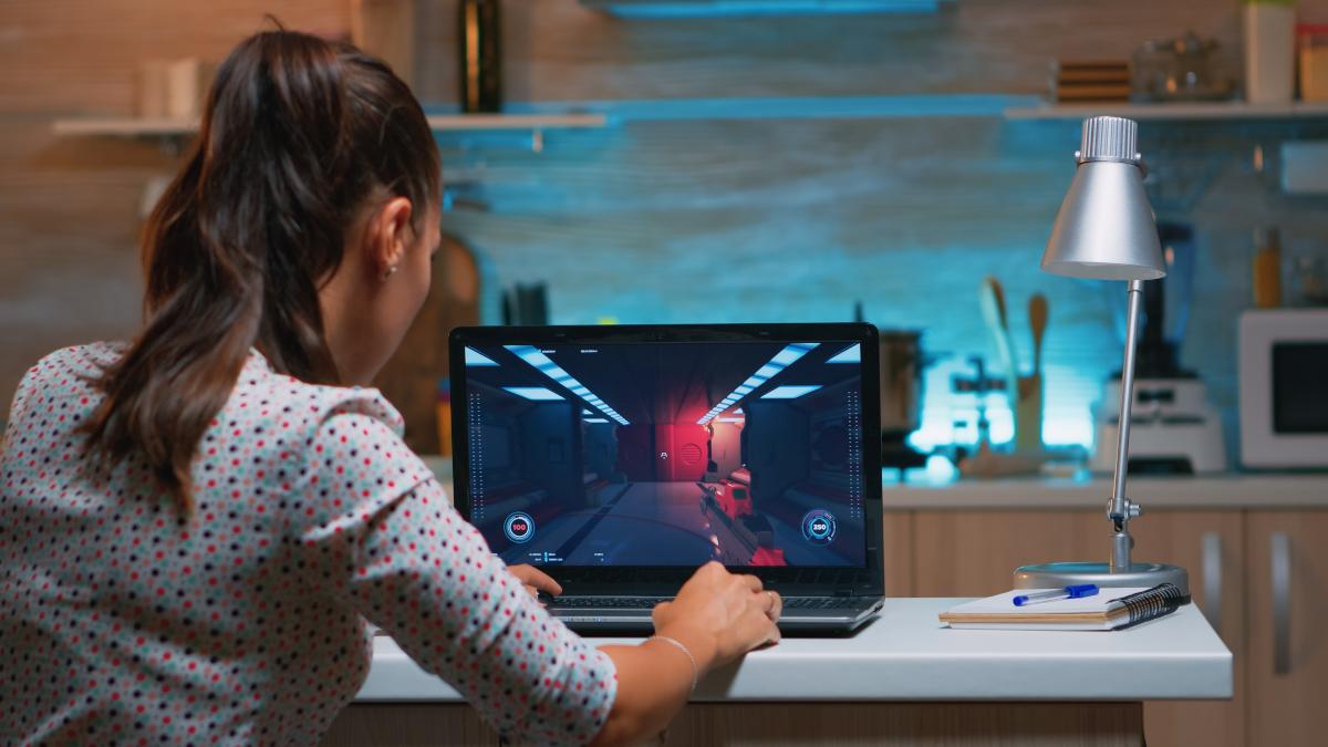 Người phụ nữ trẻ chơi game trên máy tính xách tay