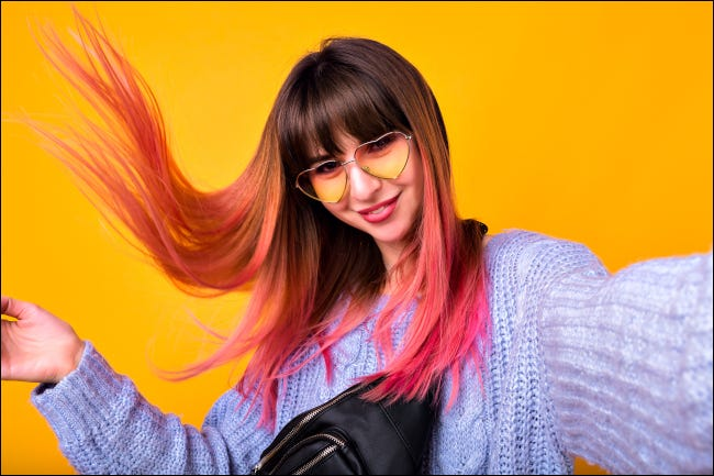 Young woman taking selfie with pink hair against yellow background in the air